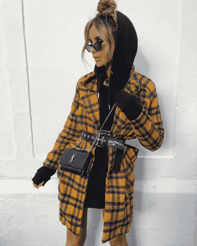 To achieve this look you need a black long hoodie with a yellow plaid coat and a gorgeous belt