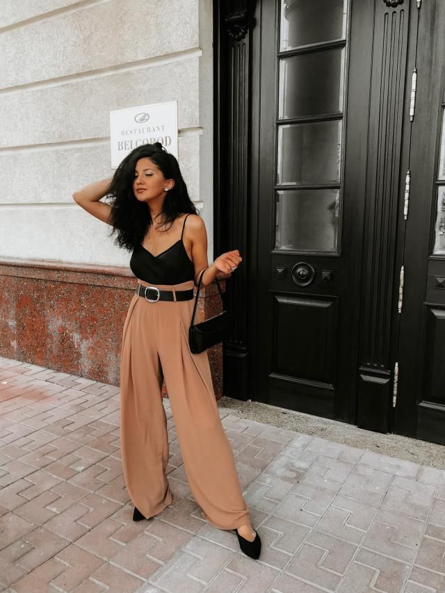 She looks chic and classy in this satin black tank top with a khaki pants