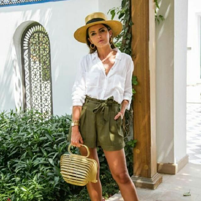 Update your casual everyday look by wearing a simple button up white blouse with green shorts and cute hat        …