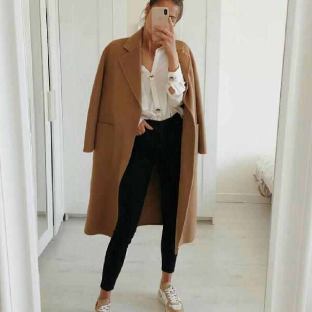For another work outfit, coordinate a black skinny jeans and white shirt with your long brown coat. Top off your l…