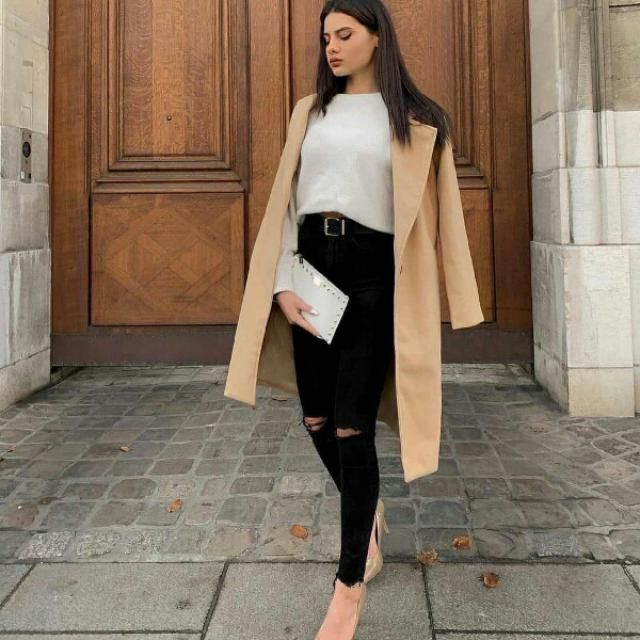 long khaki coat with simple white sweater and ripped black jeans